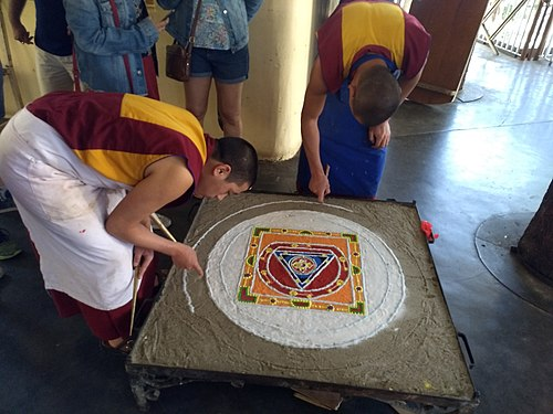 Buddhist Monks performing traditional Sand mandala made from coloured sand.jpg