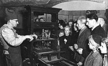 Ein Drucker in historischer Berufstracht an einem Nachbau einer Gutenbergpresse bei der Düsseldorfer Presseausstellung 1947 (Quelle: Wikimedia)