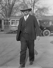 Representative Carl Hayden wearing a dark gray three piece suit and cowboy hat, walking towards the camera and smoking a cigar