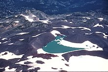 A snow-covered lake surrounded by dark glacial till