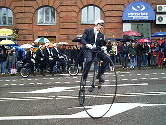 The Cortège - Students of Chalmers University of Technology in Gothenburg, Sweden, riding a penny-farthing and a quadruplet bicycle (in the background) with student caps, during the Chalmers Cortège of 2006.