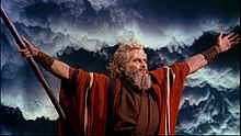 Actor playing Moses wearing a red robe and holding his arms out to the sides with dark clouds behind him