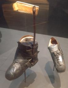 Photographie de deux chaussures prises de trois quarts, en cuir noir, la gauche étant de taille normale, la droite étant deux ou trois fois plus grande.