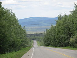 Chena Hot Springs Road at mile 14 (km 22), looking westbound and downhill, with the Little Chena River valley at the bottom.