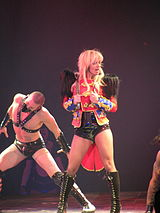 Image of a blond woman. She is standing with a red feathered jacket, carrying a whip around her neck and singing in a wireless microphone. Several people surround her, all wearing S&M outfits.