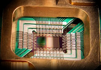 Quantum computing - Photograph of a chip constructed by D-Wave Systems Inc. Mounted and wire-bonded in a sample holder.  The D-Wave processor is designed to use 128 superconducting logic elements that exhibit controllable and tunable coupling to perform operations.