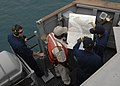 Darryl Brown, commanding officer of USS Robert G. Bradley (FFG 49), talks with a Nigerian pilot while navigating into Lagos.jpg