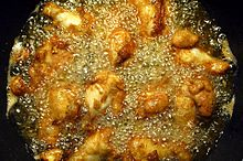 Chicken wings being cooked in a pan filled with corn oil