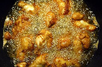 Battered chicken legs in bubbling oil.