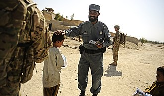 Haptic communication - An Afghan police officer pats a child on the head.
