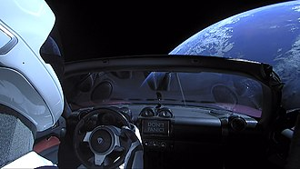 """Phrases from The Hitchhiker's Guide to the Galaxy - Elon Musk's Tesla Roadster in space with the entertainment system displaying """"DON'T PANIC"""""""