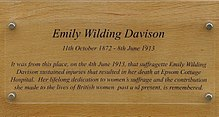 "Plaque dedicated to Davison. In addition to her name and dates, the text reads ""It was from this place, on the 4th June 1913, that suffragette Emily Wilding Davison sustained injuries that resulted in her death at Epsom Cottage Hospital. Her lifelong dedication to women's suffrage and the contribution she made to the lives of British women past and present, is remembered."