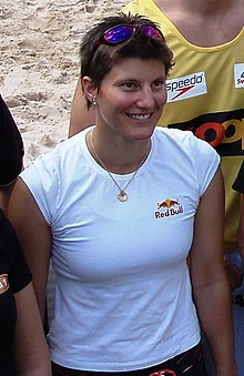 Young smiling woman with short brown hair, wearing a white T-shirt with the Red Bull logo and sleeves pulled back. She also wears a pair of sunglasses on top of her head and a golden chain with a circular pendant around her neck. She is on a beach among a group of people.