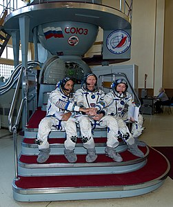 Expedition 31 crew members in front of the Soyuz TMA spacecraft mock-up in Star City.jpg