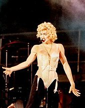 Madonna wearing a beige corset and black pants. She has blonde curly hair and has a headset microphone to her mouth