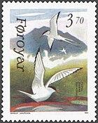 représentation d'un timbre des îles Féroé comportant deux sternes, une en vol et une au sol ailes déployées, avec comme fond une montagne