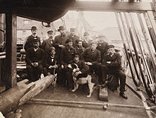 A group of 13 men and one dog pose on the cramped deck of a ship, amid ropes, spars and rigging, all wearing hats and, with one exception, dark suits.
