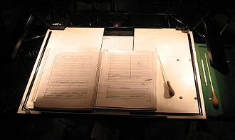 Conducting - Conductor's score and batons on a lit, extra-large conductor's music stand
