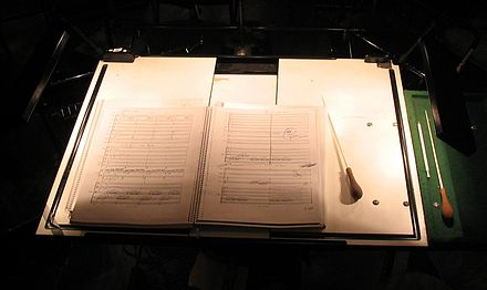 Conductor's score and batons on a lit, extra-large conductor's music stand Full score.jpg