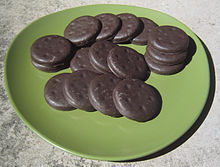Sixteen Thin Mints spread out on a green plate.
