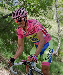 Alberto Contador climbing while wearing the pink leader's jersey