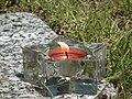 Gläserner Teelichthalter mit rotem Teelicht.JPG