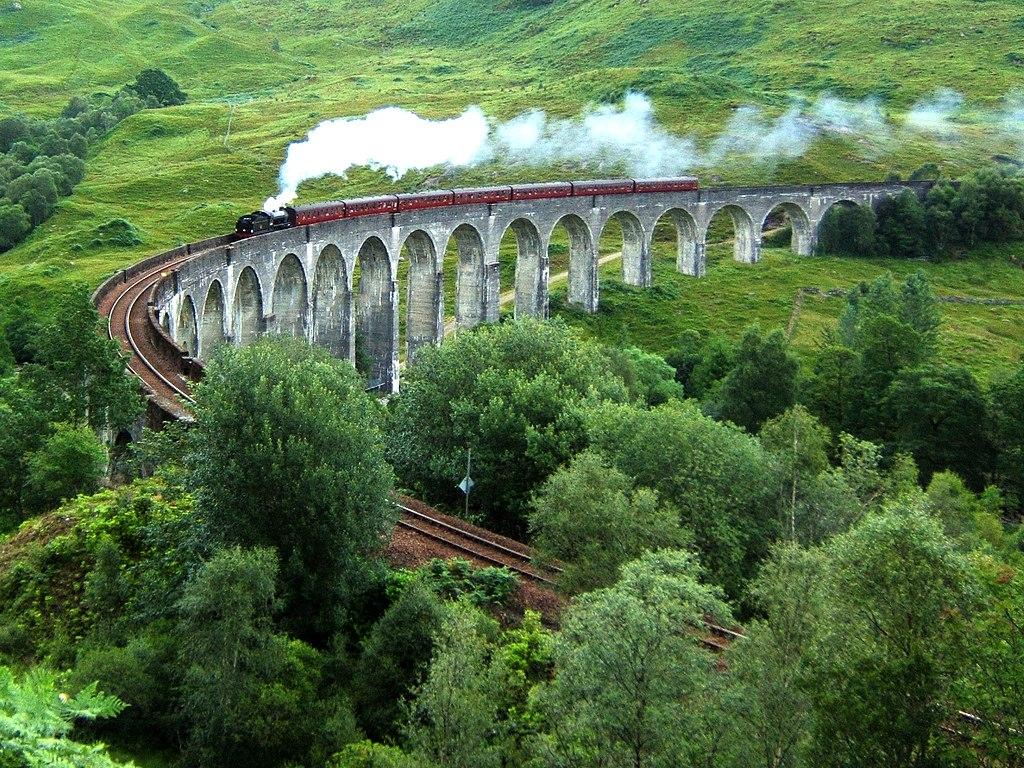 Une locomotive à vapeur tracte un train franchissant le viaduc de Glenfinnan.