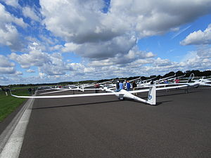 Gliding - Good gliding weather: Competitors studying  cumulus humilis, which suggest active thermals and light winds.