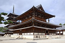 A large wooden building with a hip-and-gable main roof and a secondary roof giving the impression of a two-storied building. Between these roofs there is an open railed veranda surrounding the building. Below the secondary roof there is an attached pent roof. Behind the building there is a five-storied wooden pagoda with surrounding pent roof below the first roof.
