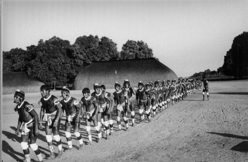 Fila de índios se apresentando para cerimônia do Kuarup (Noel Villas Boas, Wikimedia)