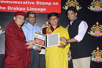 "Drukpa Lineage - Drukpa Thuksey Rinpoche, Shri SK Sinha, Member (HRD), Department of Posts, the Gyalwang Drukpa and Arjun Pandey holding the newly released stamp and first-day cover on ""The Drukpa Lineage of Buddhism"""