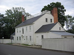 Back side of a two-story, white, clapboard house