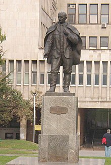 Statue of man in cape on a pedestal in front of a building