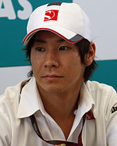 A portrait of a man in his mid-20s wearing a white T-shirt and baseball cap with the logo of the Sauber Formula One team looking to the right of the camera.