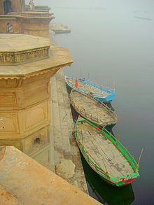 Three boats parked near steps of a ghat built in yellow stones.