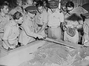 A man in uniform with peaked cap uses a pointer to draw attention to an aspect of a topographical model. A throung of men in uniforms without hats stands around him.