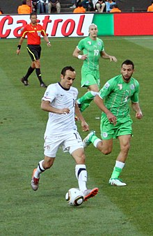 A man wearing a white shirt plays with a round ball at his feet, while being chased by two men in green shirts on a grass field.