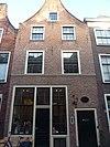 foto van Pand met tuitgevel. Tudorbogen boven vensters op tweede verdieping