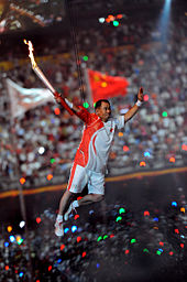 An Asian man in red and white athletic shirt and shorts, and wearing athletic shoes, is suspended by wires in the air while holding a lit torch. In the background, a large crowd in a stadium can be seen, as well as two blurred flags.