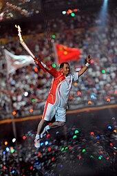 Un bărbat asiatic în cămașă și pantaloni scurți de sport roșii și albi, care poartă pantofi de sport, este suspendat de fire în aer în timp ce ține o torță aprinsă.  În fundal, se poate vedea o mulțime mare pe un stadion, precum și două steaguri neclare.
