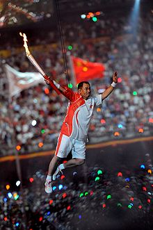 An Asian man in red-and-white athletics shirt and shorts, and wearing sneakers, is suspended by wires in the air while holding a lit torch in his right hand. In the background, a large crowd in a stadium can be seen, as well as two blurred flags hoisted in flagpoles.