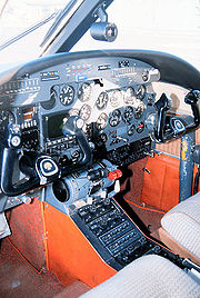 Cockpit of a light aircraft, showing instrumentation dials and dual control yokes.