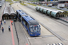 Blue articulated bus at a station