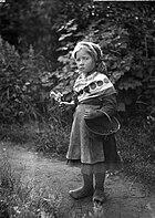 Liten flicka med korg och blommor i händerna - Nordiska Museet - NMA.0052599.jpg