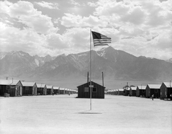 Small buildings in rows in a dusty flat area. A tattered U.S. flag flies from a pole in the foreground, and tall mountains dominate the background below a sky with clouds.