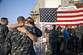 Marty Martin, an Operation Gratitude volunteer, hugs U.S. Navy Damage Controlman 1st Class Philip Hertz after giving him a care package on the guided missile cruiser USS Gettysburg (CG 64) in the Gulf of Oman 131212-N-PL185-117.jpg