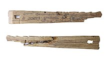 Two small pieces of wood, slightly triangular in shape; these are two halves of the same piece of wood. The top piece shows writing in old English; the lower is rougher.