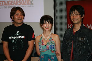 Kojima Productions - Kenichiro Imaizumi (producer), Yumi Kikuchi (model), and Hideo Kojima showcasing Metal Gear Solid 4 in 2007