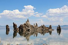 A rock formation rises from the surface of a calm lake. In the distance, the horizon is filled with hills.  The sky is blue with clouds The rocks appear grey in colour.