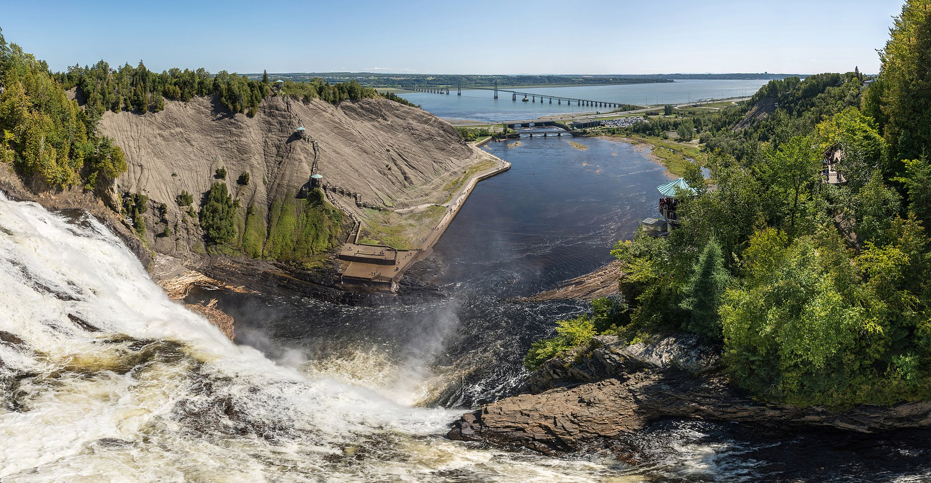 La chute Montmorency vue de l'amont, près de Boischatel. En arrière-plan, le confluent de la rivière Montmorency et du fleuve Saint-Laurent.  (définition réelle 13524×7022)